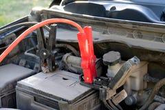 Eine Autobatterie Jumper Cables mit den kupfernen Klammern befestigt zu den Anschlüssen lizenzfreies stockbild