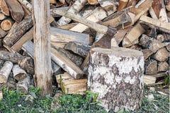 Eine Axt in einem Holzbalken vor dem hintergrund eines Stapels von woode Lizenzfreies Stockbild