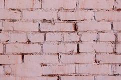 Eine Backsteinmauer beschichtete mit roter und rosa Farbe Stockbilder