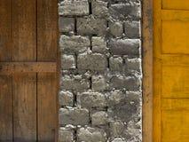 Eine Backsteinmauer zwischen den Holztüren: auf dem links ist eine alte braune Tür, auf dem Recht ist eine helle gelbe Tür, ein m Lizenzfreie Stockfotos