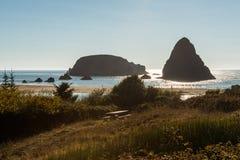 Eine Bank, die eine kleine Insel übersieht, die heraus in den Pazifischen Ozean auf einem Strand in Süd-Oregon hervorsteht, USA stockfotos