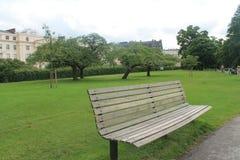 Eine Bank im Park auf einem Hintergrund des grünen Grases Lizenzfreie Stockfotos