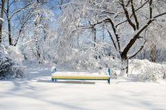 Eine Bank im Schnee unter dem Baum Lizenzfreie Stockfotografie