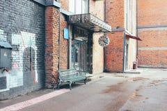 Eine Bank und eine Wanduhr nahe dem Eingang zum Speicher an der Flacon-Entwurfs-Fabrik lizenzfreies stockbild