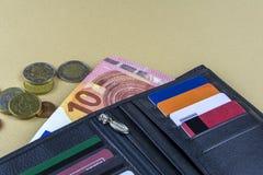 Eine Banknote des Euros 10 auf einem beige Hintergrund, einigen Münzen und einer schwarzen männlichen Geldbörse Stockbilder