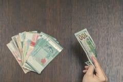 Eine Banknote von hundert US-Dollars in der Mädchen ` s Hand gegen das Bündel von Südostasien-Geld Geldumtausch in Asien Lizenzfreie Stockfotografie