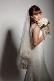 Eine beautyful Braut betrachtet unten ihrem Blumenstrauß von den Rosen. Stockbilder