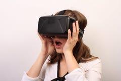 Eine beeindruckte, überraschte, verblüffte Frau, die auf Kopfhörer der virtuellen Realität Oculus-Risses VR sich entfernt oder si Stockbilder