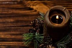 Eine beleuchtete braune Kerze wird mit einem Fichtenzweig mit kleinen Kegeln verziert Hölzerne Bretter Browns auf dem Hintergrund lizenzfreies stockfoto