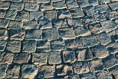 Eine Beschaffenheit der grauen Pflasterstraße als Hintergrund Lizenzfreie Stockfotografie