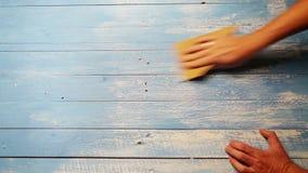 Eine beschleunigte Gesamtlänge einer Person, die das hölzerne Brett mit Sandpapier poliert, damit es älter schaut