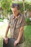 Eine besorgte alte Frau reflektiert die Stellung im Garten Stockfotos