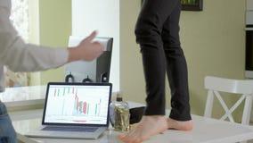Eine betrunkene Geschäftsfrau tanzt auf eine Tabelle, auf Computern einer Tabelle und einer Flasche alkagol Der Mann entfernt es  stock video footage