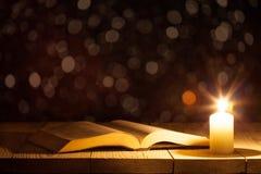 Eine Bibel auf dem Tisch angesichts einer Kerze lizenzfreie stockfotografie