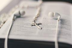 Eine Bibel ist auf einer Tabelle mit einem Kreuz und dem In-Ohr-Kopfhörer gesetztes offenes Stockbild