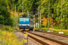 Eine blaue elektrische Lokomotive, welche die tschechische Landschaft führt stockfotografie