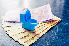 Eine blaue Spielzeugtoilettenschüssel steht auf dem Geld von ukrainischen Hryvnas lizenzfreies stockfoto