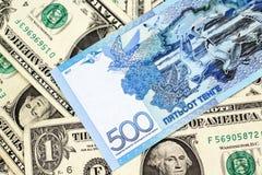 Eine blaue Tengeanmerkung von Kasachstan mit Amerikaner ein Dollarscheine stockfoto