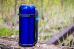 Eine blaue Thermosflasche für die Rettung von heißen Getränken Thermosflasche auf dem links Herbst Stockfoto