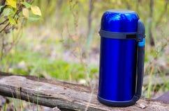 Eine blaue Thermosflasche für die Rettung von heißen Getränken Thermosflasche auf dem Recht Lizenzfreies Stockfoto
