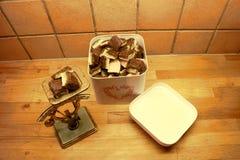 Eine Blechdose gefüllt mit selbst gemachten Süßigkeiten und eine alte rustikale Skala mit Süßigkeitenstücken auf die Oberseite lizenzfreie stockbilder