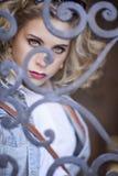 Eine blonde behaarte blauäugige junge Frau, die durch ausführliche Eisentür schaut Stockbild
