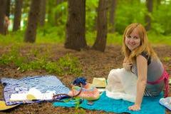 Eine blonde Dame ist in einem Kiefernwald Stockfoto