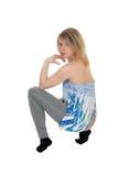 Eine blonde Frau, die auf Boden sich duckt Stockbilder