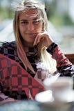 Eine blonde Frau, die in einem Café sitzt Stockbild