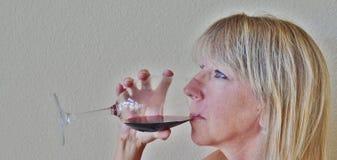 Eine blonde Frau, die einen Glas- oder Rotwein trinkt. Lizenzfreie Stockbilder