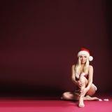 Eine blonde Frau, die in erotischer Sankt-Wäsche aufwirft Stockfotos