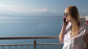 Eine blonde Frau, die mit einem Telefon auf einem Hotelbalkon nahe der Seelandschaft spricht stock footage