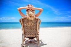 Eine blonde Frau in einem Hut sitzt auf einem Stuhl und betrachtet ein schönes Stockbild