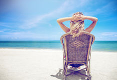Eine blonde Frau in einem Hut sitzt auf einem Stuhl und betrachtet ein schönes Stockfotografie