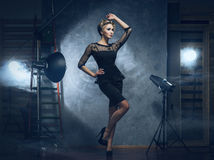 Eine blonde Frau in einem Kleid, das in einem Studio aufwirft Lizenzfreie Stockfotos