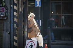 Eine blonde Frau in einem Schaffellmantel spricht am Telefon und lehnt sich an der Wand Sie runzelt in der Sonne die Stirn Lizenzfreie Stockfotos