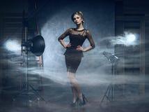 Eine blonde Frau in einem schwarzen Kleid, das in einem Studio aufwirft Stockfoto