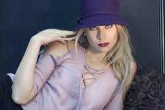 Eine blonde Frau mit blauen Augen und ein purpurroter Hut und eine Flieder schnürte sich Bluse Lizenzfreie Stockfotos