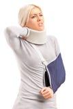 Eine blonde Frau mit dem gebrochenen Arm und verletztem Stutzen   Lizenzfreies Stockbild