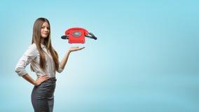 Eine blonde Geschäftsfrau steht und hält eine Handpalme mit einem roten Retro- Telefon hoch, das über ihm schwebt Stockbilder
