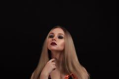 Eine blonde gotische Priesterin in der Dunkelheit Stockfotos
