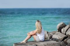 Eine blonde junge Frau, die auf einem Stein mit ihr das Meer zurück betrachtend sitzt Stockfoto