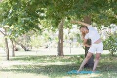 Eine blonde junge Frau, die Eignung im Park tut Lizenzfreies Stockfoto