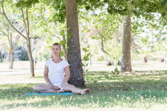 Eine blonde junge Frau, die Yoga im Park tut Stockbilder