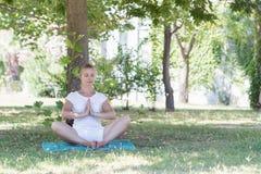 Eine blonde junge Frau, die Yoga im Park tut Stockfotos
