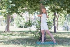 Eine blonde junge Frau, die Yoga im Park tut Stockfoto