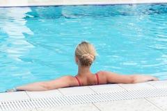 Eine blonde junge Frau in einem Swimmingpool Stockbild