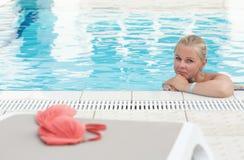 Eine blonde junge Frau in einem Swimmingpool mit rotem Bikini verließ durch das Pool Stockfotografie