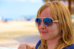 Eine blonde stilvolle Dame, die nach links schaut, ist in einem Strandcafé Stockbild