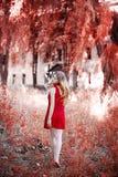 Eine Blondine in einem roten Kleid geht in den Park Lizenzfreies Stockfoto